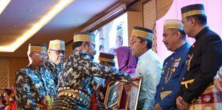 Gubernur Sulawesi Selatan Dr Syahrul Yasin Limpo saat menyerahkan penghargaan koperasi kepada Walikota Makassar Danny Pomanto. (foto: Humas)
